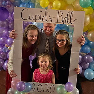 four people at the cupids ball photo station